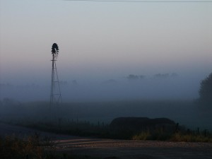 Windmill shrouded in fog at a farm outside of Walker, Iowa